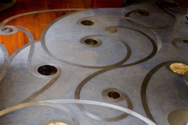 Concrete floor with stainless steel inlays and rounds in different marbles