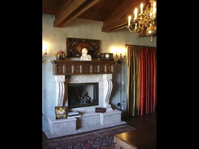 Bedroom detail with fireplace, antiques and wood ceiling with beams.