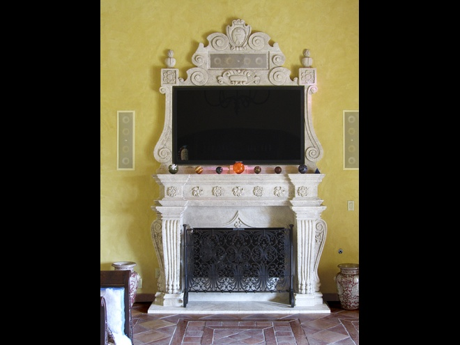 Custom limestone fireplace carved in Cyprus with wrought iron screen.