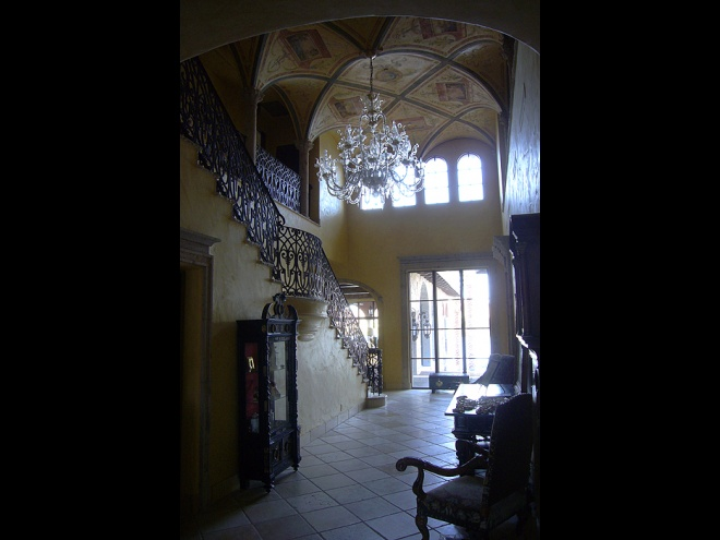 Grand gallery with Murano chandelier and wrought iron railing.