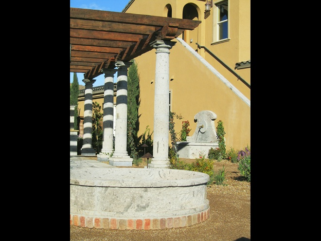 Pergola structure with fountain and stone firepit ring.